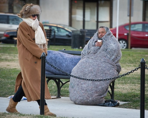 woman bundled against the cold walks past a homeless man in McPherson Square as temperatures dipped into the single digits Fahrenheit and minus degrees with the wind chill on January 7, 2014 in Washington, DC.