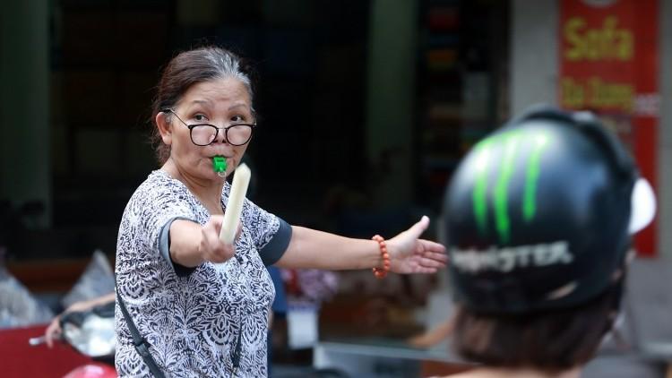 Gần 1 năm bất kể mưa nắng, người phụ nữ xuống đường điều tiết giao thông