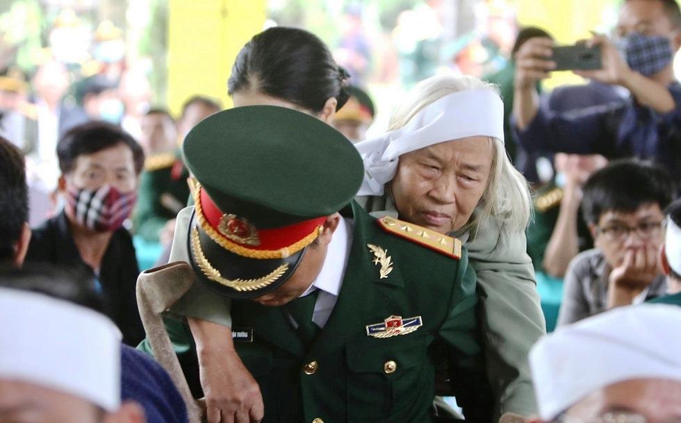 Một người thân của liệt sĩ được một thượng úy Quân nhân chuyên nghiệp quân đội cõng đến nhà tang lễ, ảnh Nguyễn Khánh