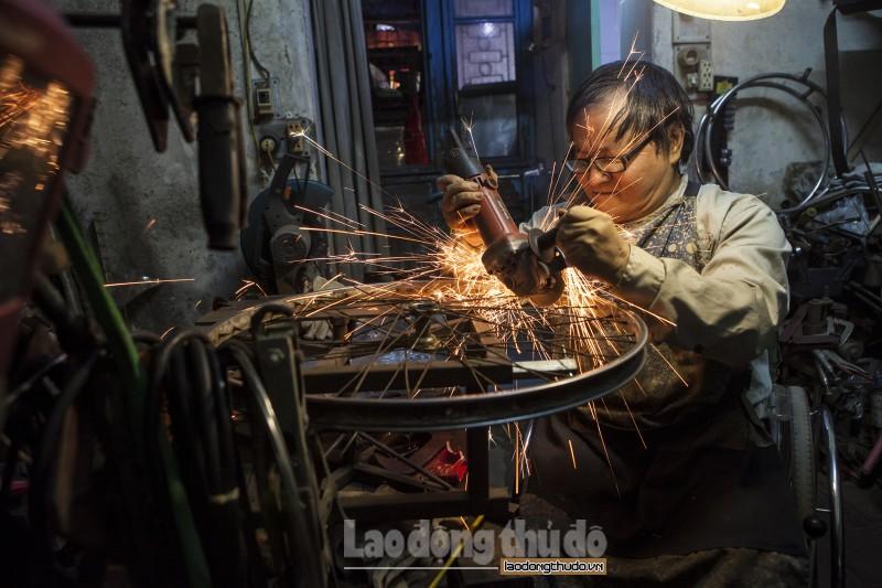 Người đàn ông ngồi xe lăn sản xuất và sửa chữa xe lăn
