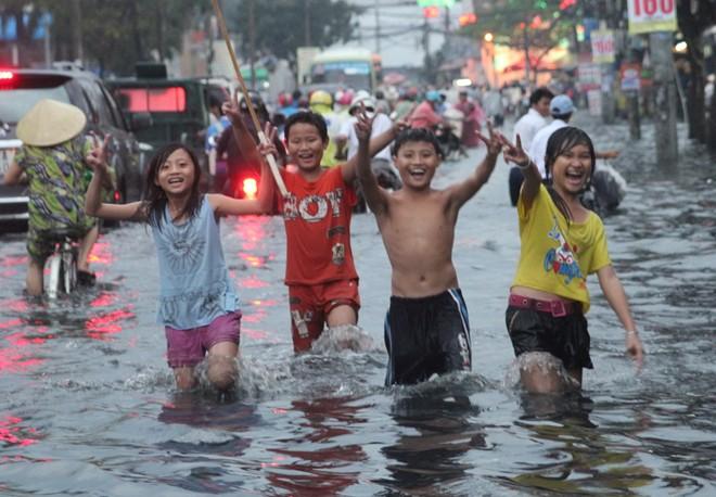 Mưa lớn, trẻ em Sài Gòn vui đùa giữa biển nước đen 8