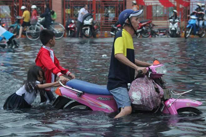 Mưa lớn, trẻ em Sài Gòn vui đùa giữa biển nước đen 14