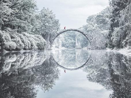 Hình ảnh này được chụp trên cây cầu Rakotzbrücke ở khu rừng phía đông nước Đức. Để tìm ra cây cầu và chụp được khoảnh khắc đẹp tới huyền ảo này, tác giả đã phải đi bộ ròng rã trong cái lạnh thấu xương băng qua rừng và ngôi làng biệt lập với trải nghiệm không thể nào quên.