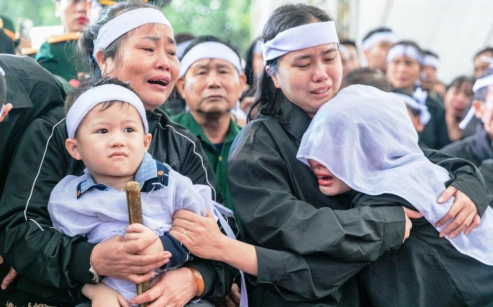 Người thân liệt sĩ Đinh Văn Trung nhiều lần khóc lịm trong đám tang. Trước ánh mắt của những đứa con còn rất nhỏ của các liệt sĩ, nhiều người dự đám tang cũng không kìm được nước mắt. Ảnh: Đức Anh