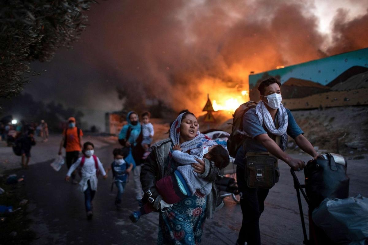 Những người di cư chạy trốn khỏi đám cháy tại trại tị nạn Moria trên đảo Lesbos, Hy Lạp ngày 9/9. Vụ hỏa hoạn đã thiêu rụi trại tị nạn lớn nhất châu Âu, khiến khoảng 12.000 người không có nơi trú ẩn. Ảnh: AP