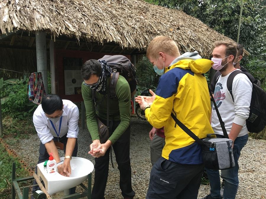 Khách du lịch thực hiện rửa tay sát khuẩn trước khi vào tham quan
