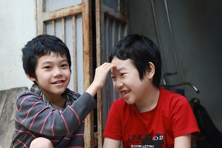 Hòa và Bình chơi đùa trước cửa nhà trọ. Ảnh Nguyễn Long